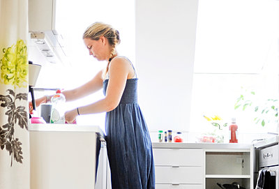 Woman doing the dishes - p312m1493647 by Rebecca Wallin