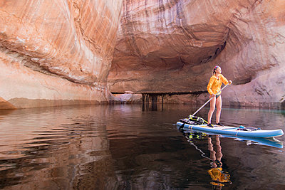 Woman paddleboarding in Lake Powell through Cathedral in the Desert, Glen Canyon, Utah, USA - p343m1578141 by Suzanne Stroeer