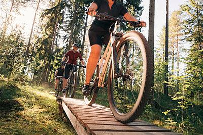 Female friends mountain biking on boardwalk by trees in forest - p426m2036738 by Katja Kircher
