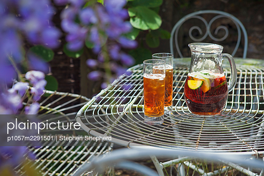 A jug of what could be Pimms a traditional fruit punch served in the summer in the Uk, sitting on an old iron table in the summer sunshine undernetah an arbor laden with flowers and plants in this typical british summertime scene. - p1057m2291501 by Stephen Shepherd