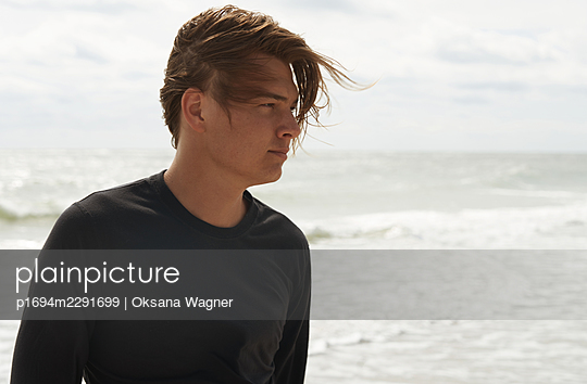 Contemplative young man in black t-shirt looking at the ocean on a windy day - p1694m2291699 by Oksana Wagner