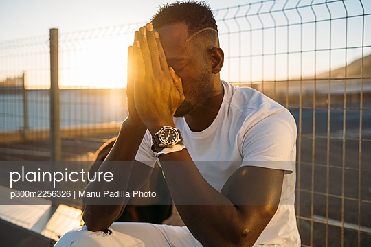 Thoughtful man with hands clasped sitting against fence - p300m2256326 by Manu Padilla Photo