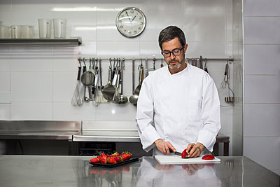 Chef slicing strawberries with kitchen knife - p1166m2130319 by Cavan Images