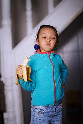Cute girl at home eating banana - p1577m2150663 by zhenikeyev