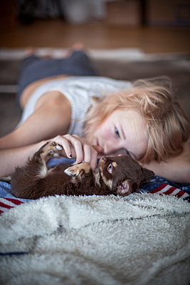 Teenage girl lying on floor and playing with puppy - p312m1121582f by Christina Strehlow