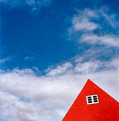 Red building against sky - p312m993075f by Lena Oritsland