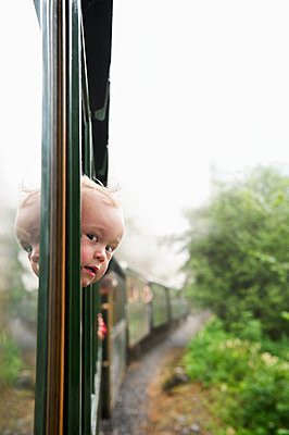 Austria, Boy (2-3) looking through train window - p352m1126593f by Julia Sjöberg
