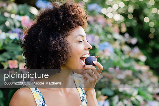 MId adult woman eating figwhile standing in front of flowering plant at park - p300m2226373 by Nicole Matthews