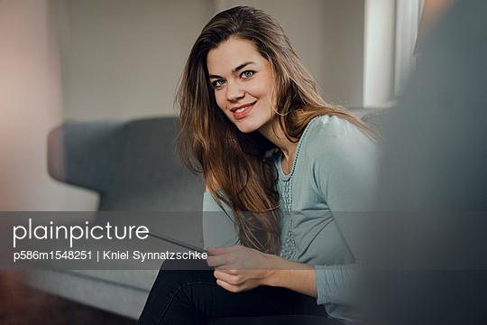 Junge Frau mit Tablet Computer zuhause - p586m1548251 von Kniel Synnatzschke
