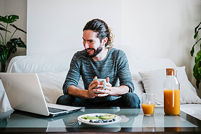 Young man with coffee cup using laptop while having breakfast sitting on sofa at home - p300m2242523 by Eva Blanco