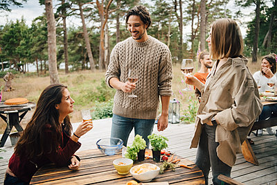 Smiling friends enjoying drinks while talking during garden party in yard - p426m2149263 by Maskot