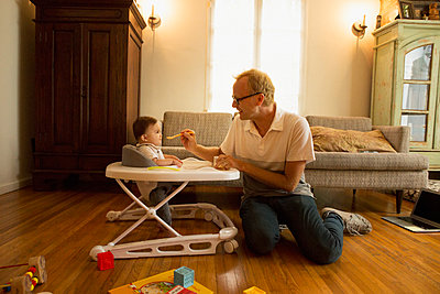 Father feeding son in high chair in living room - p555m1410933 by Lucy von Held