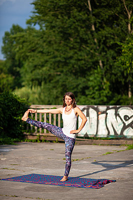 Young woman practicing yoga in park - p795m2199804 by JanJasperKlein