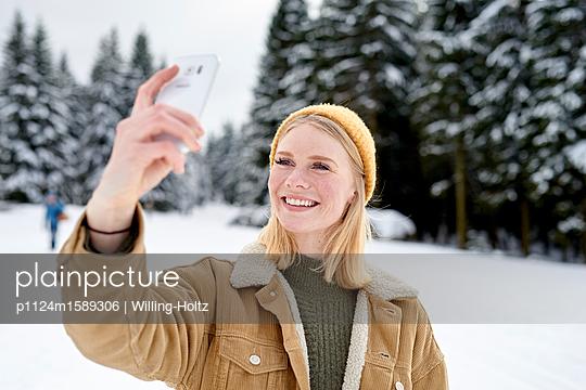 Junge Frau macht ein Selfie im Schnee - p1124m1589306 von Willing-Holtz