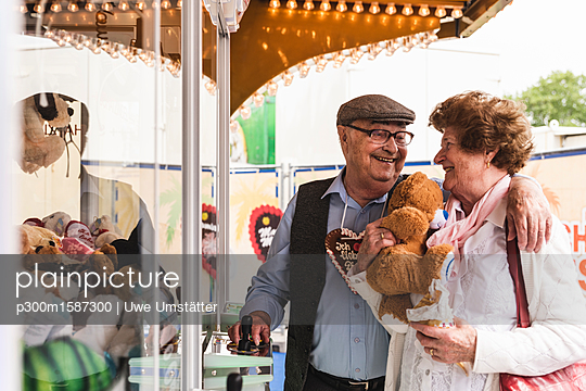 Happy senior couple with prize on fair - p300m1587300 von Uwe Umstätter