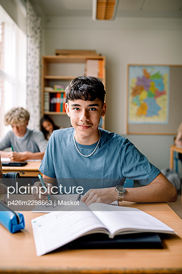Portrait of teenage boy drawing on book in classroom - p426m2298663 by Maskot