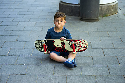 Portrait of astonished little boy sitting on pavement with skateboard - p300m2004635 by Benjamin Egerland
