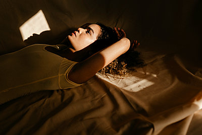 Portrait of Brazilian woman lying on cloth at home with sunlight on her face - p300m2181152 von Tania Cervián