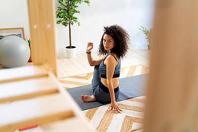 Woman with curly hair doing spinal twist pose at home - p300m2275431 by Giorgio Fochesato