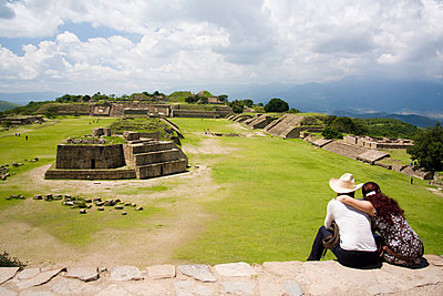 A young couple looks out over the Zapotec ruins of Monte Alban - p3433369 by Ethan Welty