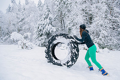 Woman rolling tire through snow - p924m1230214 by Pete Saloutos