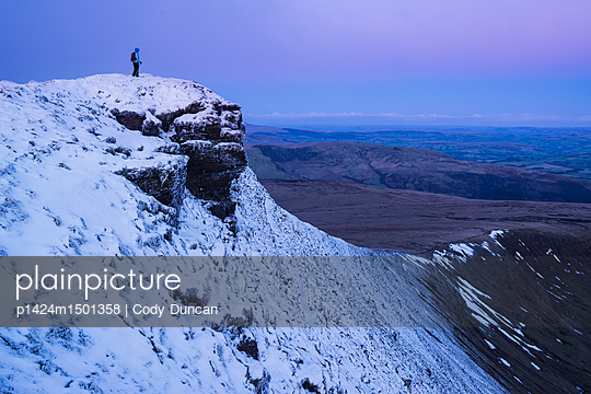 Female hiker on snow covered summit of Corn Du at dawn, Brecon Beacons national park, Wales - p1424m1501358 by Cody Duncan