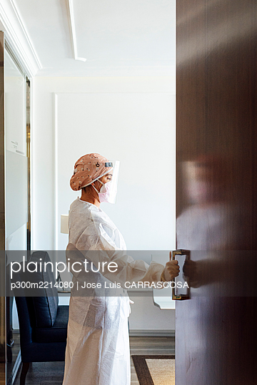 Doctor in protective suit standing by door at office - p300m2214080 by Jose Luis CARRASCOSA