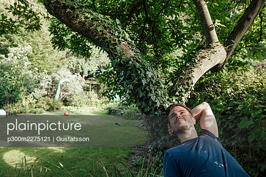 Man relaxing on tree branch in backyard during sunny day - p300m2275121 by Gustafsson