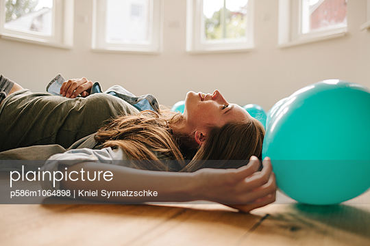 Young woman in new apartment with balloons - p586m1064898 by Kniel Synnatzschke