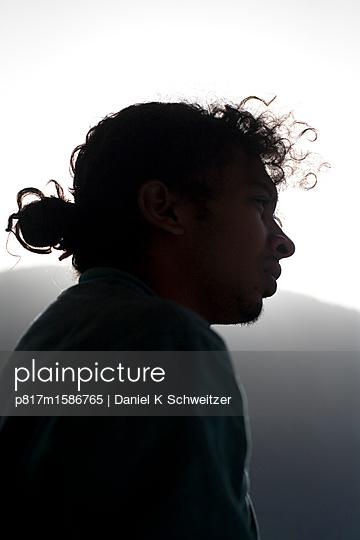 Junger Mann im Gegenlicht - p817m1586765 von Daniel K Schweitzer
