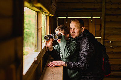 Boy and father birdwatching with binoculars - p300m1450212 by Nicole Matthews