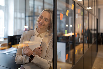 Mature businesswoman with closed eyes leaning against glass pane in office - p300m2154960 by Gustafsson