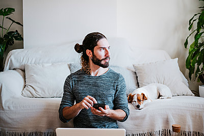 Man with laptop and mobile phone looking away while sitting by dog sleeping on sofa at home - p300m2242337 by Eva Blanco