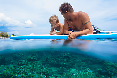Father and son with surf board in ocean,Bali,Indonesia - p343m1578166 by Konstantin Trubavin