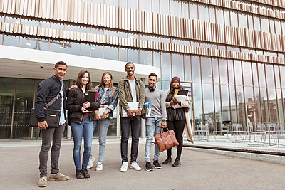 Full length portrait of smiling multi-ethnic students standing against building in campus at university - p426m2072222 by Kentaroo Tryman