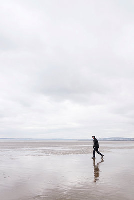 Man walking on beach at low tide - p597m1425605 by Tim Robinson