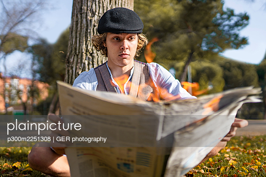Surprised young man reading lit newspaper while sitting against tree in park - p300m2251308 by GER photography