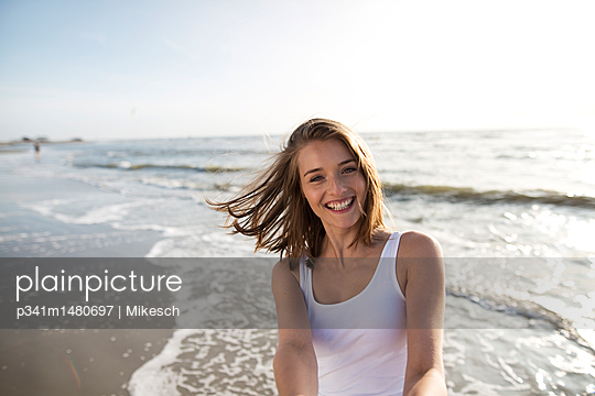 Young woman on St. Peter-Ording beach - p341m1480697 by Mikesch