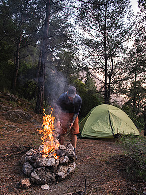 Man burning campfire near tent amidst trees in forest in the evening - p1166m2107726 by Cavan Images