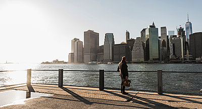 USA, Brooklyn, back view of businessman with briefcase looking at Manhattan skyline - p300m1206316 by Uwe Umstätter