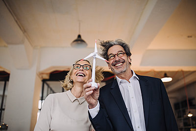 Happy businessman and businesswoman holding wind turbine model in office - p300m2154948 by Gustafsson