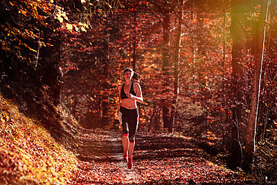 Woman jogging in autumn forest - p300m2166367 by Studio 27