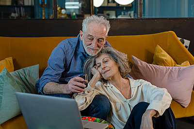 Senior couple talking over video call on laptop while sitting on sofa at home - p300m2265125 by Emma Innocenti