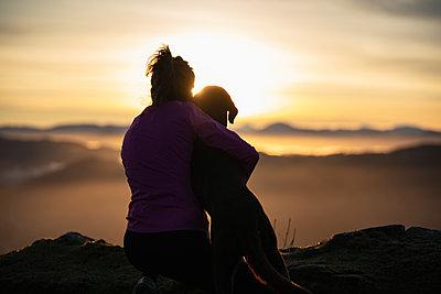 young girl with her dog contemplating the sunrise, San Sebastian, Spain - p300m2277634 von SERGIO NIEVAS
