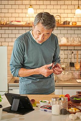 Japanese senior man in the kitchen - p307m2023360 by Yosuke Tanaka