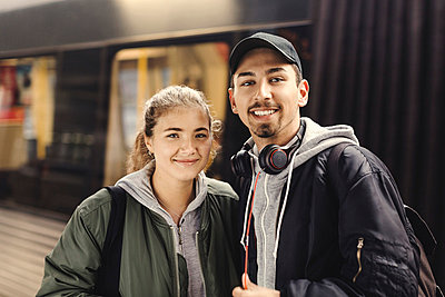 Portrait of happy young couple standing at subway station - p426m1003759f by Maskot