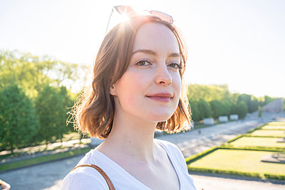 Portrait of young woman with brunette hair standing in a park, smiling at camera. - p429m2208594 by Tamboly