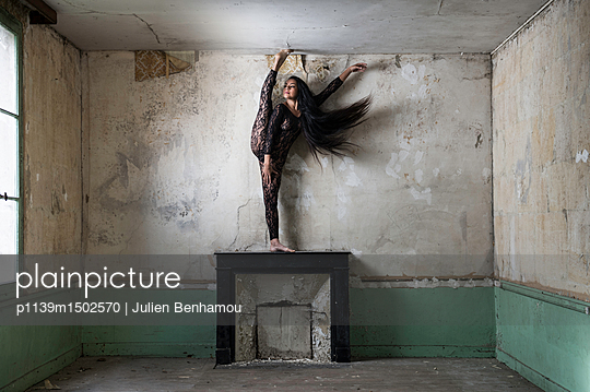 Female dancer with long black hair on mantelpiece - p1139m1502570 by Julien Benhamou
