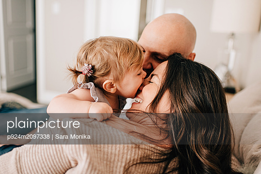 Mother and father reclining on bed together with baby daughter, over the shoulder view - p924m2097338 by Sara Monika