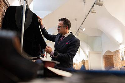 Mature dressmaker measuring jacket on rail - p1166m2261418 by Cavan Images
